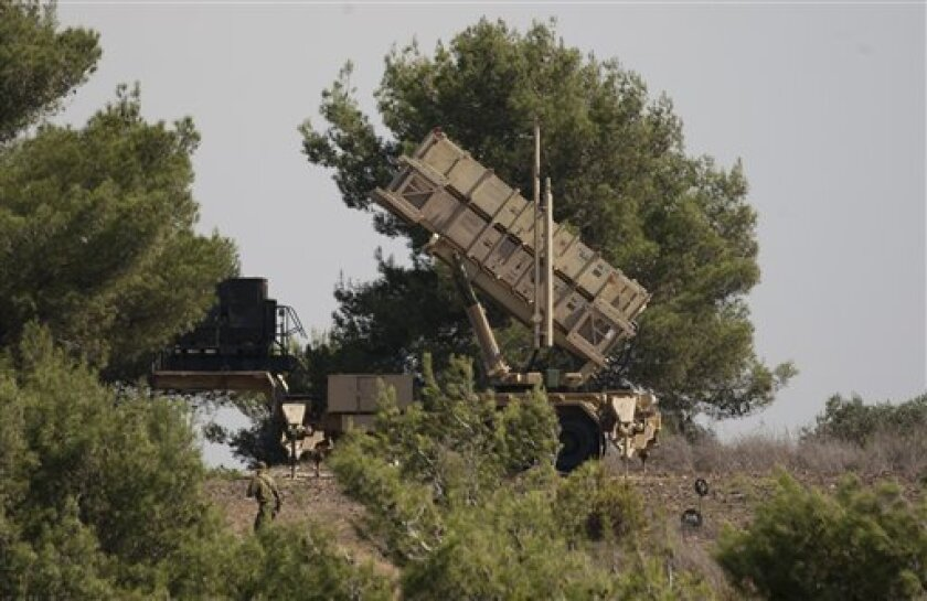 An Israel soldier walks past a Patriot missile defense battery positioned on the Carmel Mt. in northern Israel, Tuesday, Oct. 9, 2012. Israel's military has deployed a missile defense system near the Lebanese border, days after warplanes shot down a mysterious unmanned aircraft that entered its skies. An army spokesman said on Tuesday that the Patriot missile defense battery was deployed in the northern city of Haifa. He refused to say if the battery's deployment was connected to Saturday's drone incident. The drone is widely believed to have originated in Lebanon. (AP Photo/Ariel Schalit)