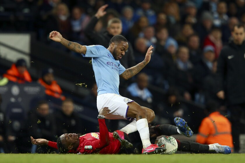 Manchester United's Aaron Wan-Bissaka, on the ground, tackles Manchester City's Raheem Sterling during the English League Cup semifinal second leg soccer match between Manchester City and Manchester United at Etihad stadium in Manchester, England, Wednesday, Jan. 29, 2020. (AP Photo/Dave Thompson)