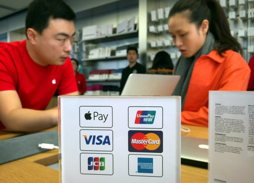 An employee works on a laptop computer as he talks with a customer near a sheet showing accepted methods of payment, including Apple Pay, top left, at an Apple Store in Beijing, Thursday, Feb. 18, 2016. Apple Inc. on Thursday launched its smartphone-based payment system in China where the electroni