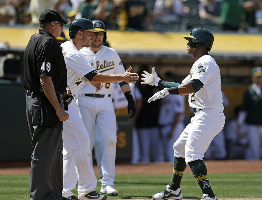Oakland Athletics' Khris Davis, right, is congratulated by Danny Valencia after hitting a three-run home run off Detroit Tigers' Alex Wilson in the seventh inning of a baseball game Saturday, May 28, 2016, in Oakland, Calif. Home plate umpire Andy Fletcher (49), left, looks on. (AP Photo/Ben Margot