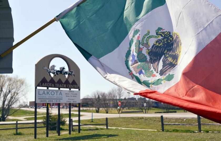 ARCHIVO - En imagen de archivo del 1 de mayo de 2015, una bandera de México ondea afuera del restaurante de comida mexicana La India Bonita frente al Centro Comercial Lakota en Kyle, Dakota del Sur, en la reserva nativa Pine Ridge. El crecimiento de la población hispana en EEUU desaceleró considerablemente durante los últimos siete años, reveló un estudio dado a conocer el jueves 8 de septiembre de 2016. (AP Foto/Russell Contreras, archivo)