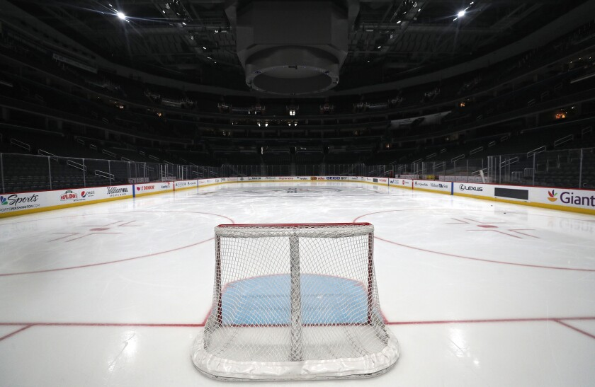 View from behind the net of an empty hockey rink.