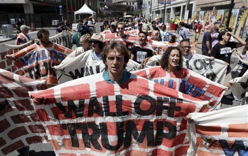 Activistas a favor de los derechos de los inmigrantes sostienen una lona que simboliza un muro en rechazo a la política migratoria de Donald Trump frente al estadio donde se celebra la convención republicana, el miércoles 20 de julio de 2016 en Cleveland. (AP Foto/Patrick Semansky)