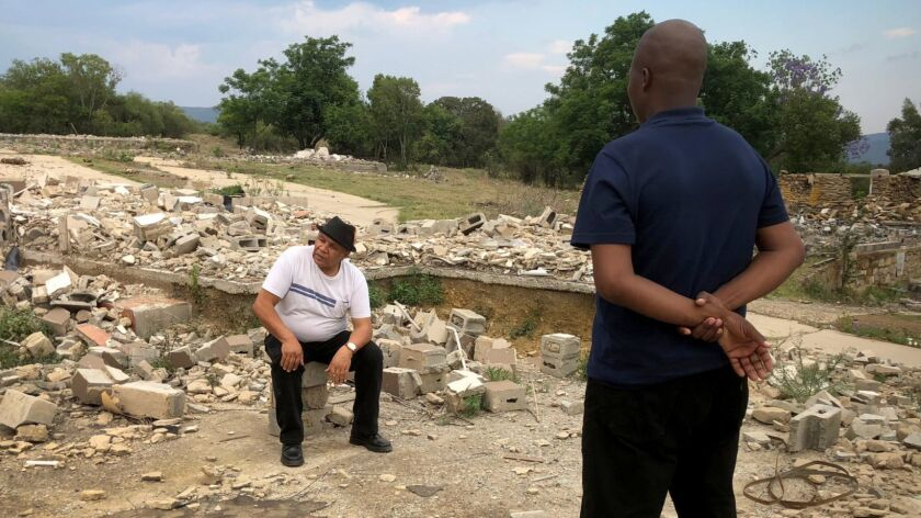 Raymond Trollip, chair of the uThukela District Land Reform Committee, surveys the rubble of a facto
