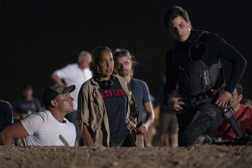 """This image released by Netflix shows director Gina Prince-Bythewood, center, with actor Luca Marinelli, right, during the filming of """"The Old Guard."""" The action film, also starring Charlize Theron, premieres this week on Netflix. (Aimee Spinks/Netflix via AP)"""
