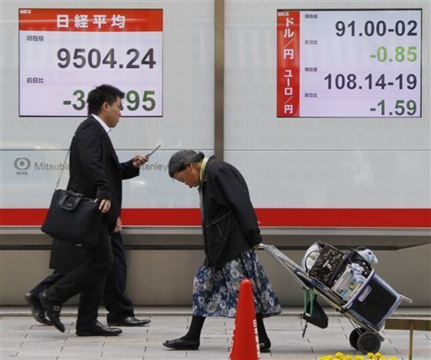 An eldery woman walks past electronic stock boards displaying the Nikkei stock average, left, and the foreign exchange quotations of the Japanese yen to the euro and the U.S. dollar at a securities firm in Tokyo, Monday, June 7, 2010. (AP Photo/Koji Sasahara)