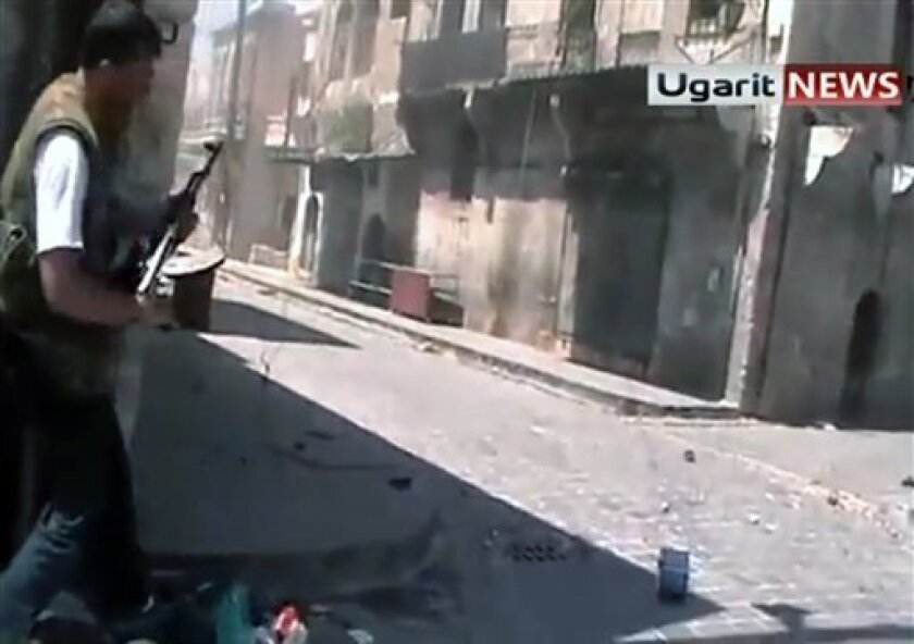 In this frame grab made from amateur video provided by Ugarit News, taken on Sunday, Aug. 26, 2012, purports to show a member of the rebel group, the Unification Brigade, as he prepares to fire his weapon at a group of Assad soldiers in street fighting in Aleppo, Syria. (AP Photo/Ugarit News via AP