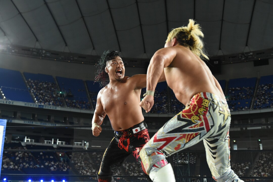 Two bare-chested male pro wrestlers in colorful pants face off in the ring.