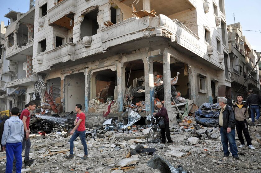 People walk by damaged buildings near at the site of a twin bomb attack in Homs, Syria, on Feb. 21.