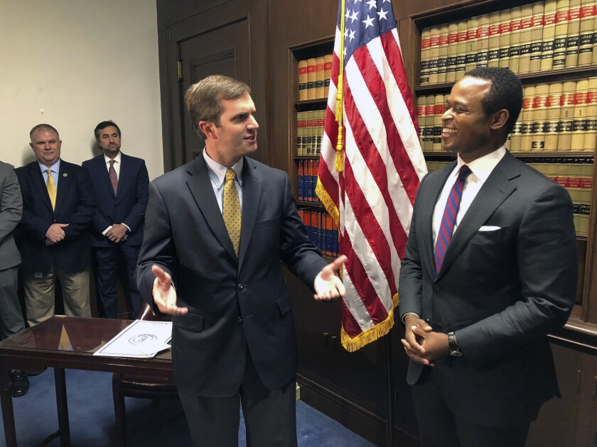 FILE - In this Dec. 17, 2019, file photo, Kentucky Gov. Andy Beshear, left, talks about the role of attorney general in Frankfort, Ky., shortly before Daniel Cameron, right, is sworn in as Kentucky's attorney general. Partisan bickering is nothing new in Kentucky, but tensions are ratcheting up as coronavirus cases continue to rise. Beshear, a Democrat, is fending off legal challenges from Cameron, a Republican, over his executive actions during the pandemic. (AP Photo/Bruce Schreiner, File)