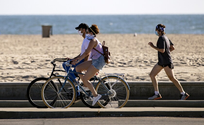 Bicyclists and a runner wear masks on the boardwalk in Santa Monica