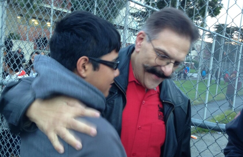 """Stuart Lutz, right, a South Gate Middle School art teacher, returned to class Wednesday after being cleared of wrongdoing in a case that drew attention to the LAUSD's """"teacher jail"""" system. Those welcoming him back include former student Armando Chavez, now in high school."""