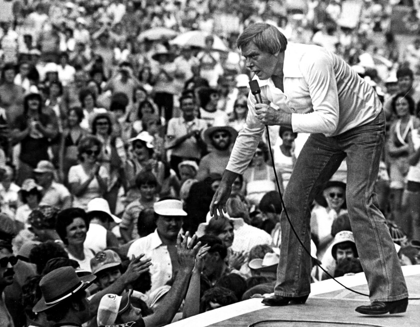 Tom T. Hall performing on stage to a large crowd in 1977.