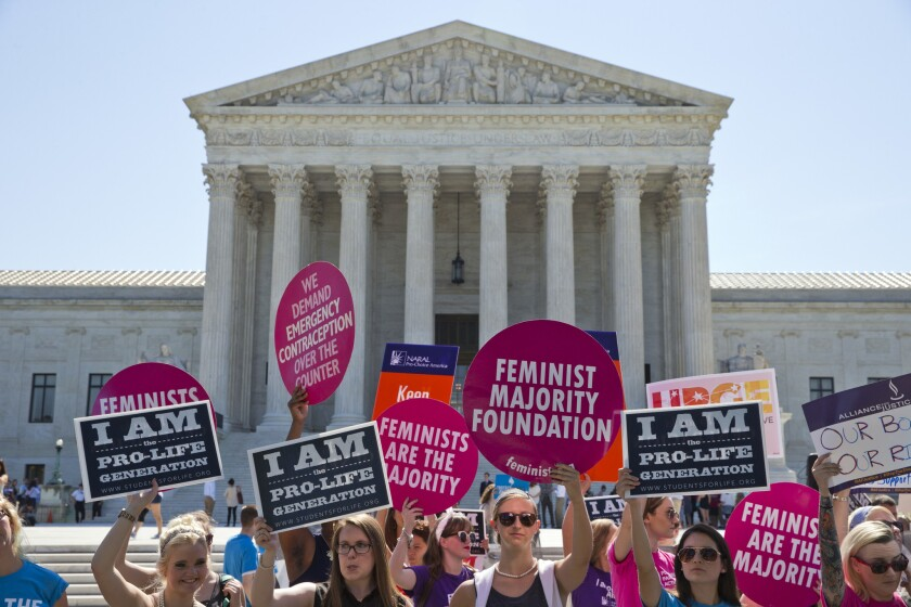 Demonstrators on both sides of the abortion issue stand in front of the Supreme Court in Washington, D.C., on Monday, June 20, 2016, as the court announced several decisions.