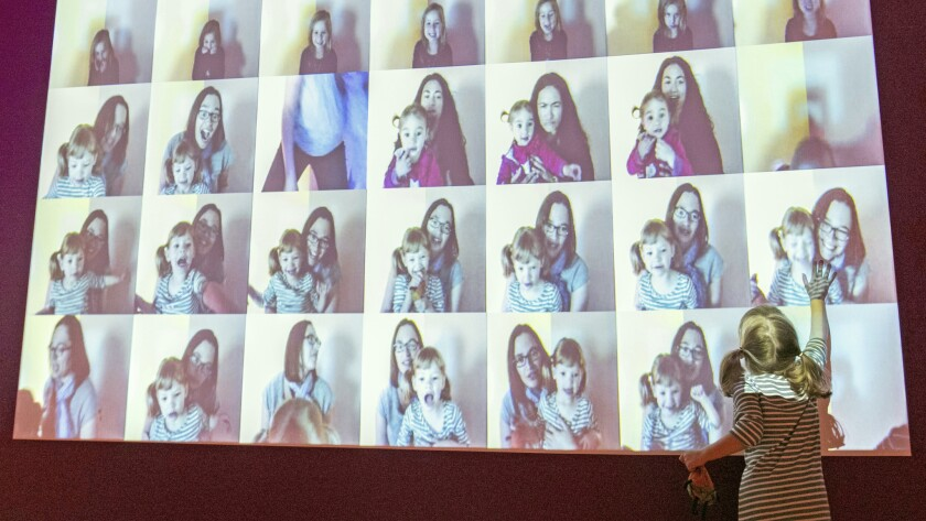At a video wall in the Canadian Museum of Human Rights in Winnipeg, a girl watches short videos of the faces she earlier made with her mother. The activity is designed to show children how their expressions convey how they are feeling.