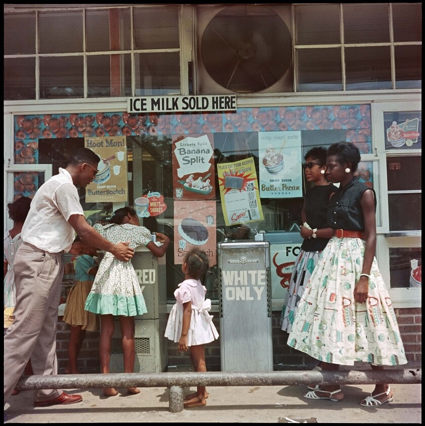 """A Black man helps a little girl drink from a """"Colored"""" drinking fountain in 1956."""