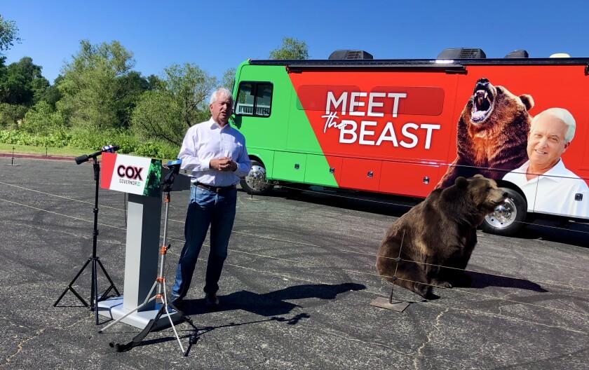 Republican gubernatorial candidate John Cox stands near a 1,000-pound Kodiak bear in a parking lot.
