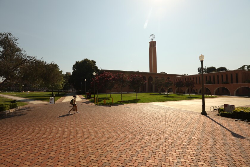 A lone student walks across an empty section of the USC campus.