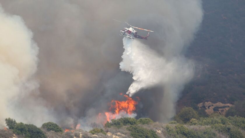 An Orange County Fire Authority helicopter makes a drop in 2018.