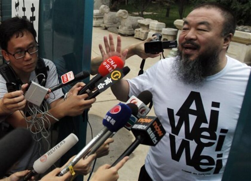 Activist artist Ai Weiwei gestures while speaking to journalists gathered outside his home in Beijing, China, Thursday, June 23, 2011. Ai, the most high-profile target of a sweeping crackdown on activists in China, has returned home late Wednesday after nearly three months in detention. The official Xinhua News Agency said Ai confessed to tax evasion, accusations his family had long denied and which activists had denounced as a false premise for detaining him. (AP Photo/Ng Han Guan)