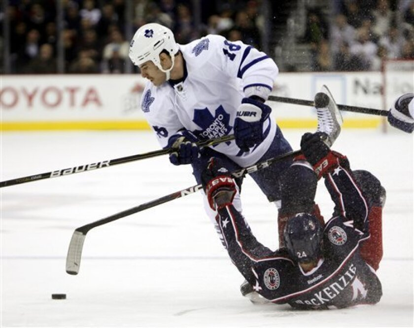 Toronto Maple Leafs' Mike Brown (18) knocks Columbus Blue Jackets' Derek MacKenzie (24) to the ice during the first period of an NHL hockey game, Thursday, Nov 3, 2011, in Columbus, Ohio. (AP Photo/Terry Gilliam)