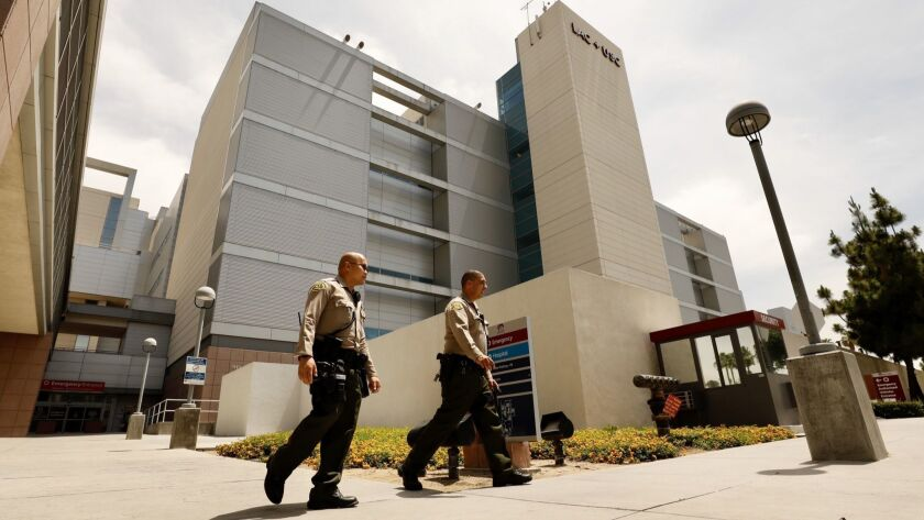 "Los Angeles County sheriff's deputies outside L.A. County-USC Medical Center, where a deputy remains in ""grave condition"" after being shot in the head on Monday."