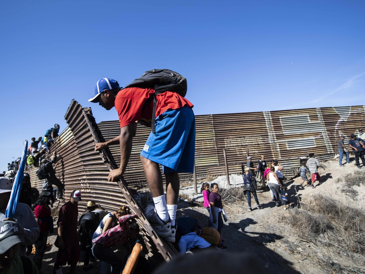A group of Central American migrants -- mostly Hondurans -- climb a metal barrier on the U.S.-Mexico border in Tijuana.