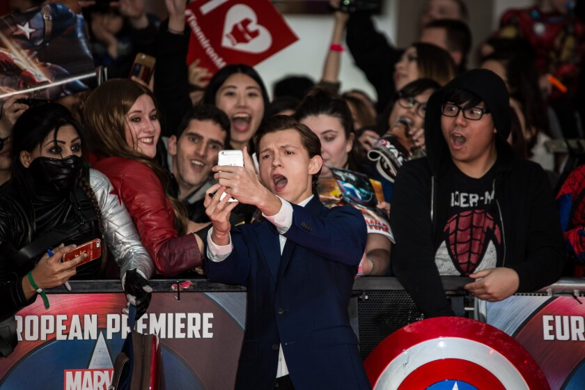 "Tom Holland takes selfies with fans at the European premiere of ""Captain America: Civil War"" in London on April 26, 2016."