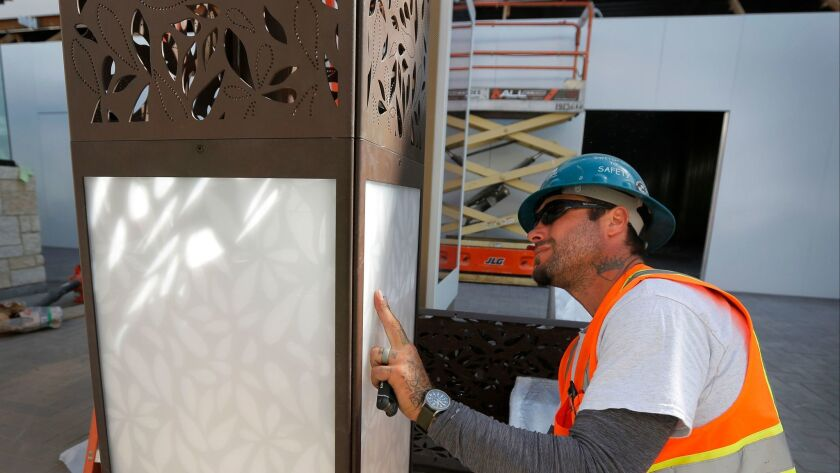 Electrician Luke Garrett installs one of the many light totems, a tall decorative light being installed in the public areas, part of the expansion and construction at the Westfield UTC shopping mall that began opening last fall.