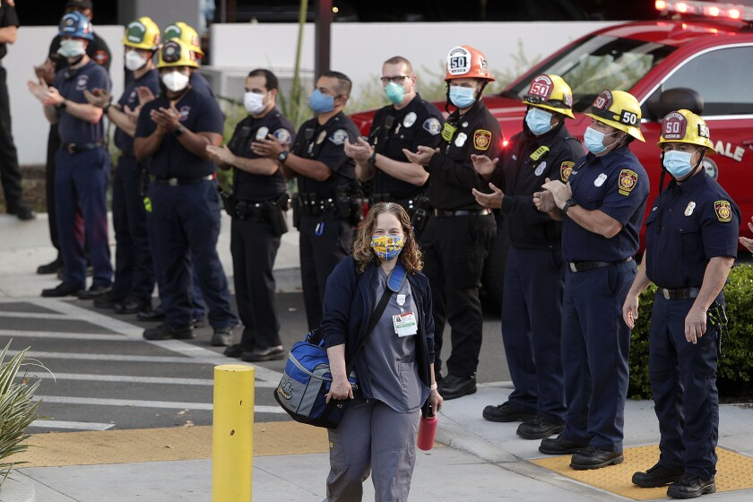 Erica Fitzgibons, a nurse practitioner at Dignity Health Glendale Memorial Hospital, smiles as she arrives to work on Thursday as members of the Glendale fire and police departments cheer on health-care workers dealing with the coronavirus pandemic.