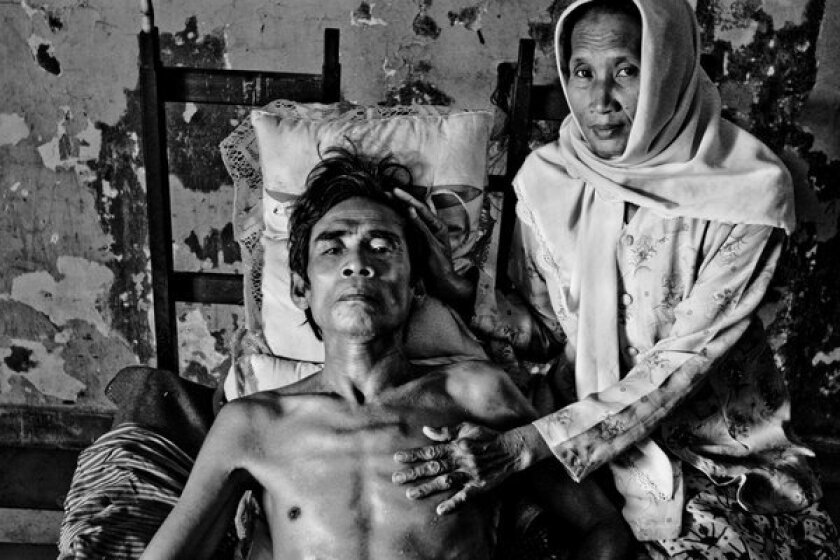 A woman waits by her husbands side in the AIDS and TB ward of The Russian Hospital, Phnom Penh, Cambodia December 8, 2004. Although he is suffering from carcinoma after 41 years of smoking, he is kept in the AIDS and TB ward which is where most impoverished patients end up.