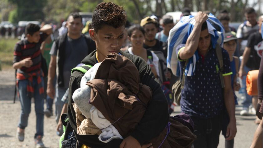 Central American migrants, part of the caravan hoping to reach the U.S. border, move on a road in Ta