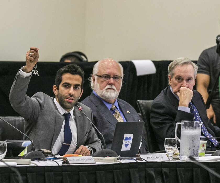 University of California Student Regent Abraham Oved holds his Star of David necklace as he comments on a proposed intolerance statement during Thursday's regents meeting at UC Irvine. At center is Regent William De La Pena and at right is Regent George Kieffer. (AP Photo/Damian Dovarganes)