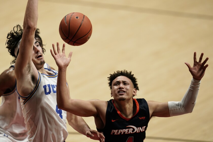 Pepperdine guard Colbey Ross (right) loses the ball as UCLA guard Jaime Jaquez Jr. defends.