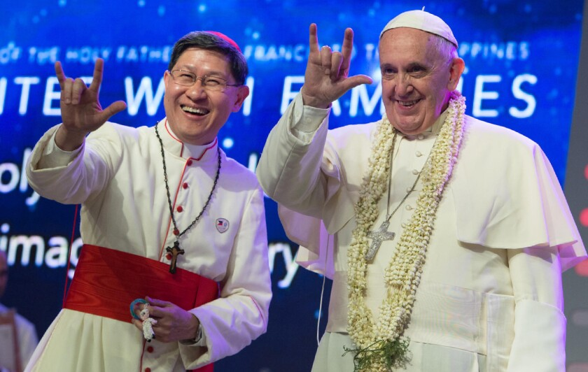 """Pope Francis and Manila Archbishop Luis Antonio Tagle salute the crowd with the popular hand sign for """"I love you"""" in the Philippines."""