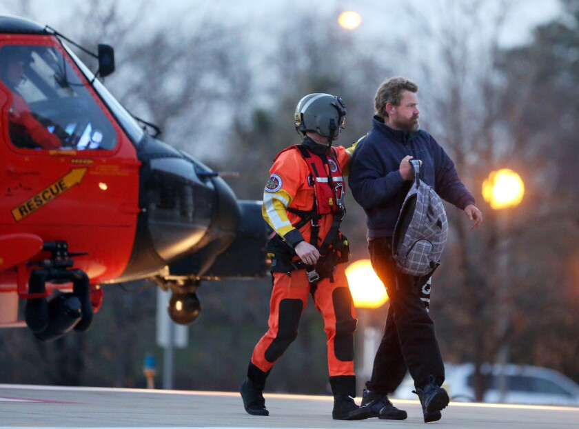 Louis Jordan, right, walks from the Coast Guard helicopter to the Sentara Norfolk General Hospital in Norfolk, Va., after being found off the North Carolina coast Thursday after two months adrift.