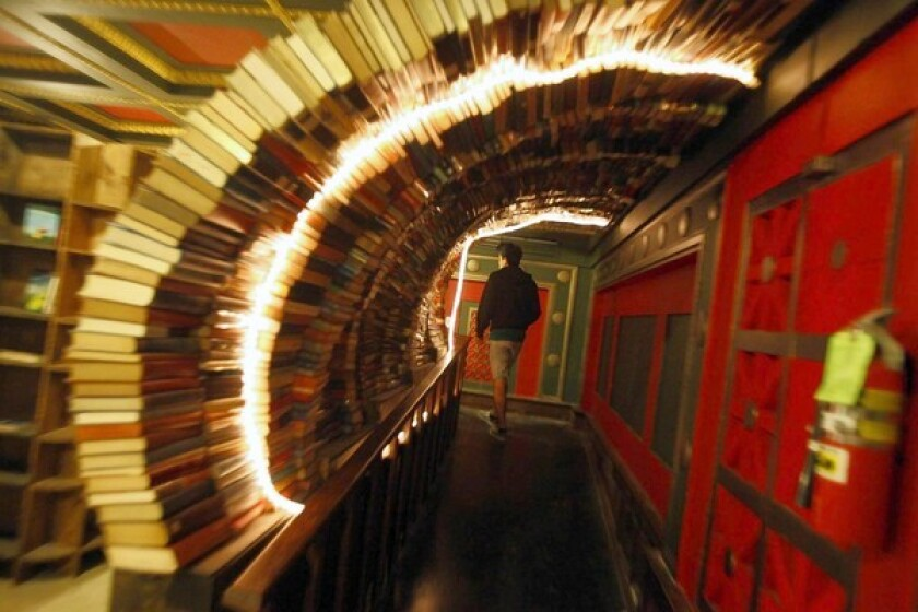 A man walks through an archway made of books in the Last Bookstore.