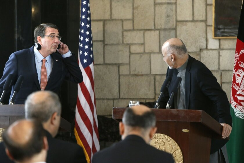 U.S. Defense Secretary Ash Carter, left, listens to remarks by Afghan President Ashraf Ghani during a news conference at the Presidential Palace in Kabul, Afghanistan, Saturday, Feb. 21, 2015. Carter made his international debut Saturday with a visit to Afghanistan to see American troops and commanders, meet with Afghan leaders and assess whether U.S. withdrawal plans are too risky to Afghan security. (SAP Photos/Jonathan Ernst, Pool)