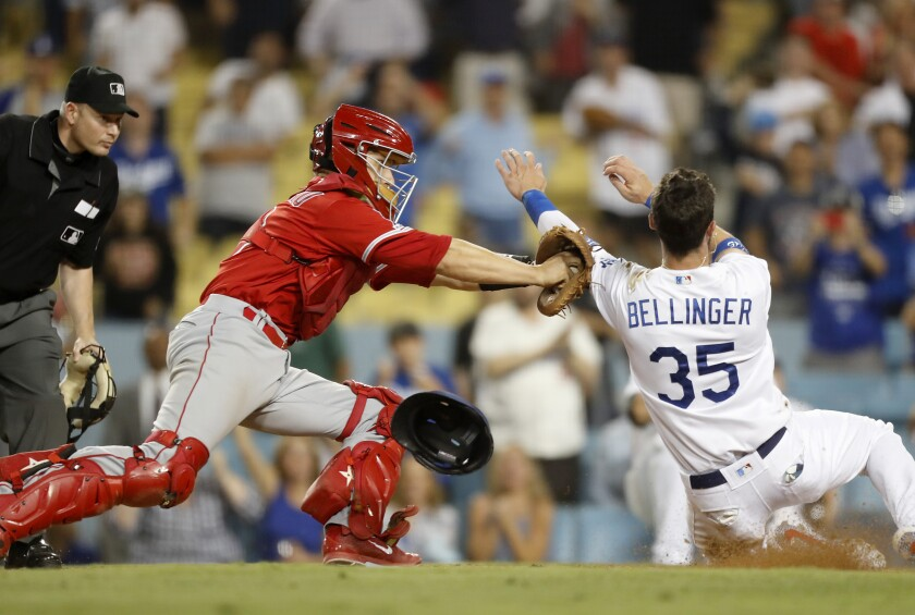 Angels catcher Dustin Garneau puts a tag on Dodgers right fielder Cody Bellinger for the final out of the game on Tuesday at Dodger Stadium.