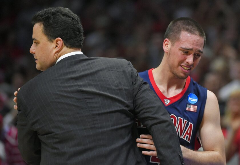 Arizona guard T.J. McConnell hugs head coach Sean Miller as McConnell leaves the game late in the second half of a college basketball regional final against Wisconsin in the NCAA Tournament, Saturday, March 28, 2015, in Los Angeles. Wisconsin beat Arizona 85-78 to advance to the Final Four. (AP Pho