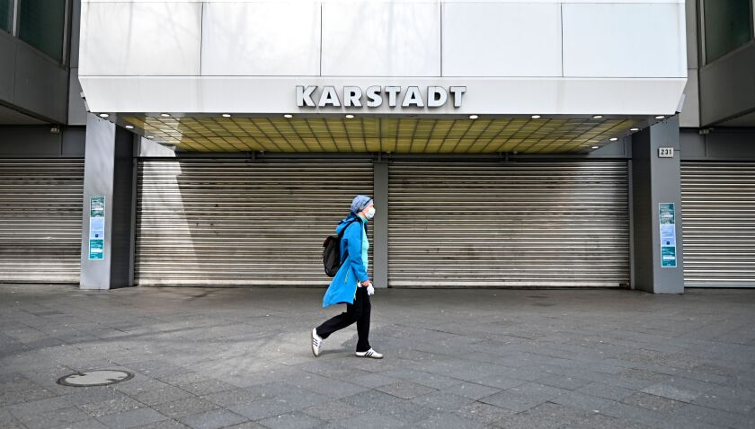 A woman wearing a face mask walks past a closed department store in Berlin on March 18, 2020.