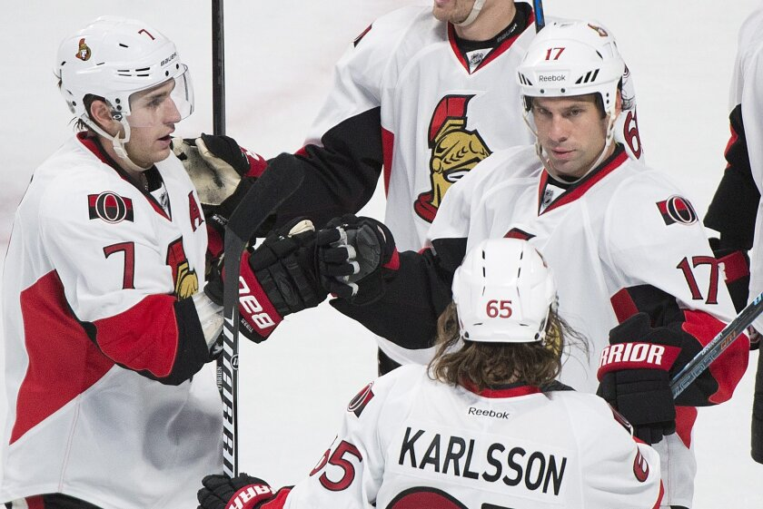 Ottawa Senators' David Legwand (17) celebrates with teammates Kyle Turris, left, and Erik Karlsson after scoring against the Montreal Canadiens during the third period of an NHL preseason hockey game Saturday, Oct. 4, 2014, in Montreal. (AP Photo/The Canadian Press, Graham Hughes)