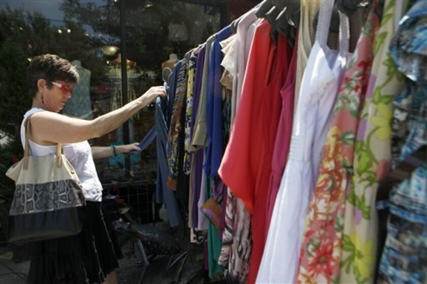 In this Wednesday, June 12, 2013 file photo, Jani McAllister browses through a sales rack outside Festivity, a boutique in Virginia Highlands, in Atlanta. The Federal Reserve reports how much consumers borrowed in June on Wednesday, Aug. 7, 2013. (AP Photo/Jaime Henry-White)