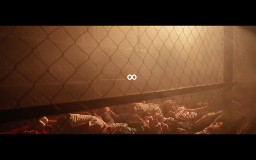 A film still shows a group of children lying down in a cage in a smoky penumbre.