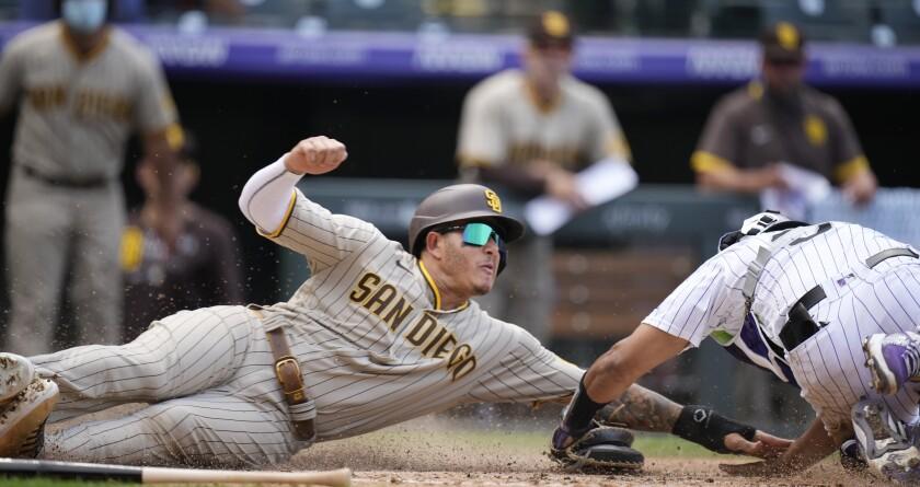 Colorado Rockies catcher Elias Diaz tags out San Diego Padres' Manny Machado as he tries to score