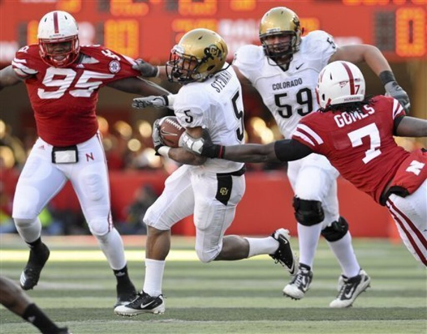 Colorado running back Rodney Stewart (5) comes under pressure from Nebraska defensive back DeJon Gomes (7), with Colorado offensive linesman David Bakhtiari (59), engaging Nebraska defensive end Pierre Allen (95) during the first half of an NCAA college football game, in Lincoln, Neb., Friday, Nov.