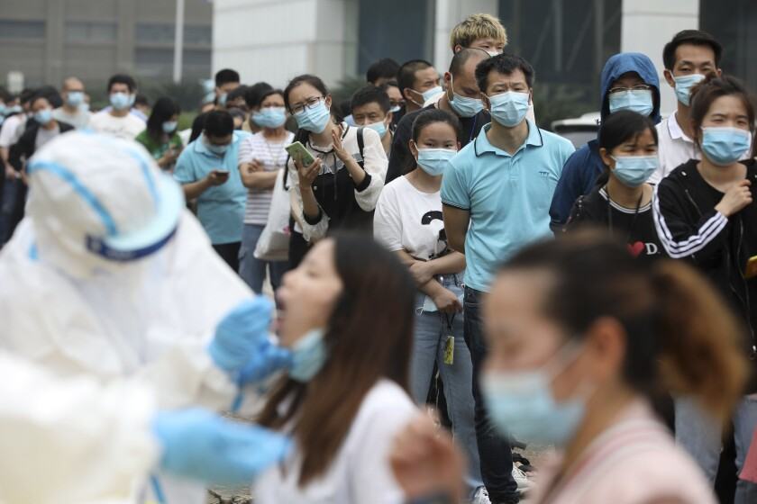 People line up for coronavirus testing at a large factory in Wuhan, China.