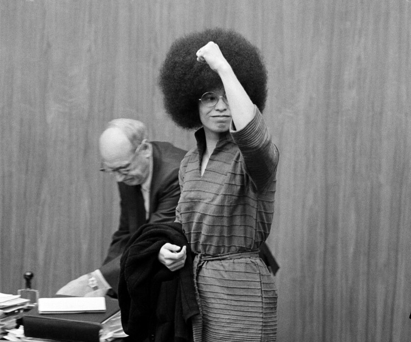 Angela Davis puts her fist in the air as she arrives in court in San Rafael, Calif., on June 28, 1971, for a pretrial hearing.