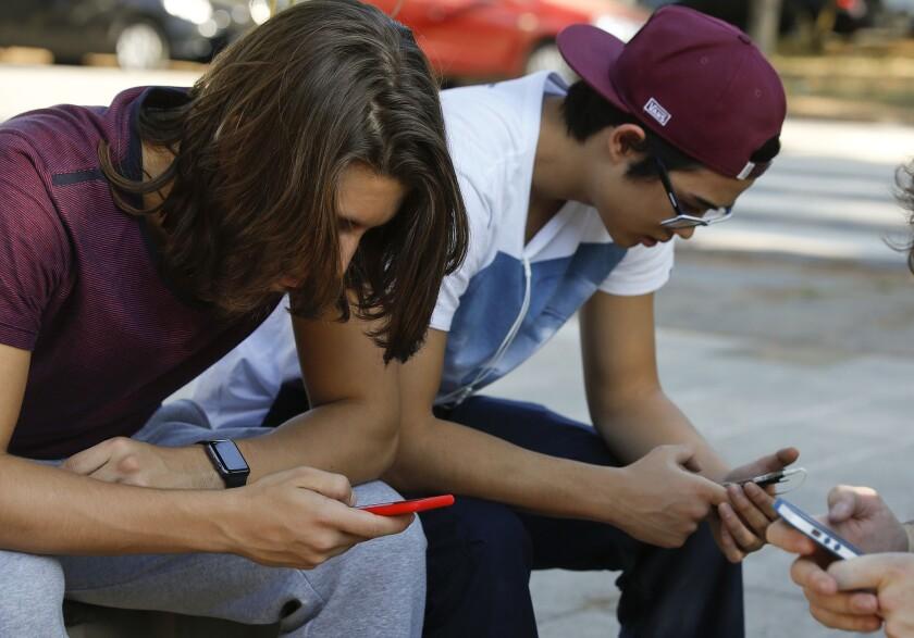 Brazilians check their cellphones in Sao Paulo on Monday.