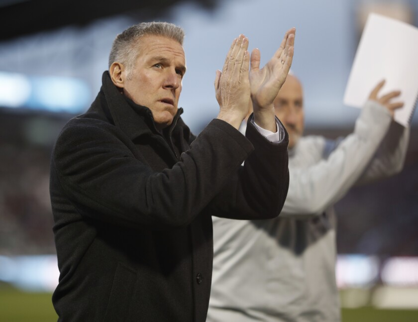 FILE - In this March 24, 2018, file photo, Sporting Kansas City's Peter Vermes acknowledges fans as he takes the pitch to lead his team against the Colorado Rapids in an MLS soccer match in Commerce City, Colo. Major League Soccer coaches are welcoming the opportunity to use five substitutes when play resumes in Florida next month, out of concern for both player fitness and the summertime heat. The adoption of the rule and the expansion of game-day rosters are especially important given the relatively short preparation time teams have had for the MLS Is Back Tournament, which starts July 8, 2020, at the sports complex at Walt Disney World. (AP Photo/David Zalubowski, File)